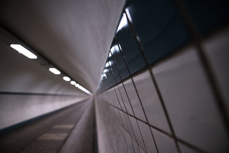 Close-up of tiled wall in illuminated tunnel