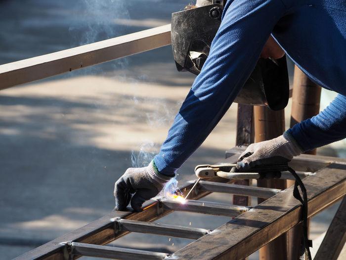 Man on welding metal at workshop
