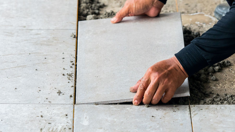 Low Section Of Man Cementing Paving Stone
