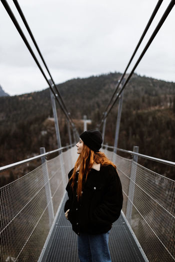 Rear view of woman standing on railing against sky