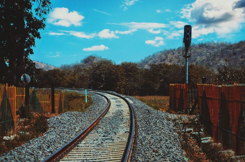 Empty railroad tracks by trees against sky