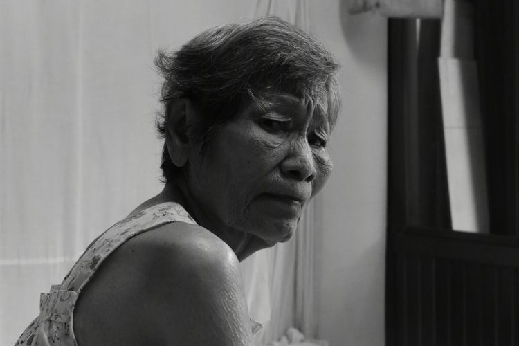 Side view portrait of wrinkled senior woman at home