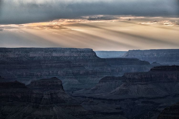 Rocky Mountains At Grand Canyon Against Cloudy Sky During Sunset