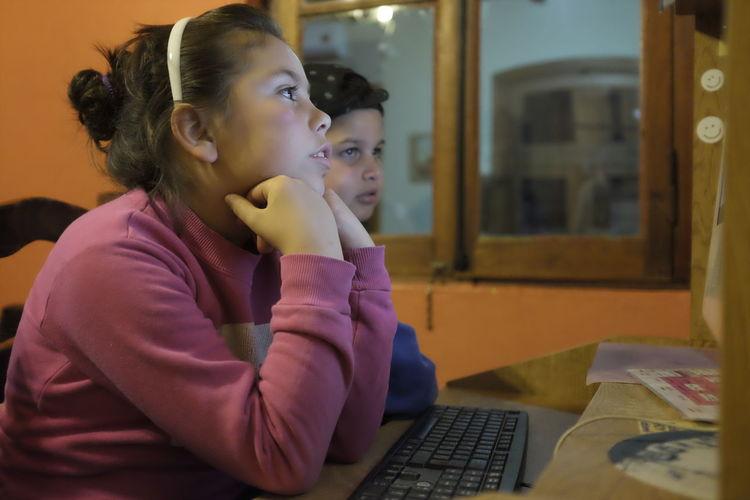 Siblings Using Computer At Home