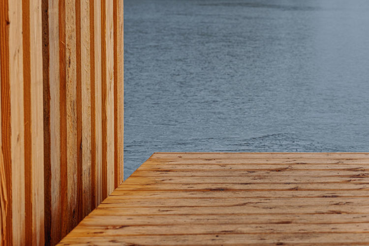 Part of wooden landing stage with wall of wooden boat house over water