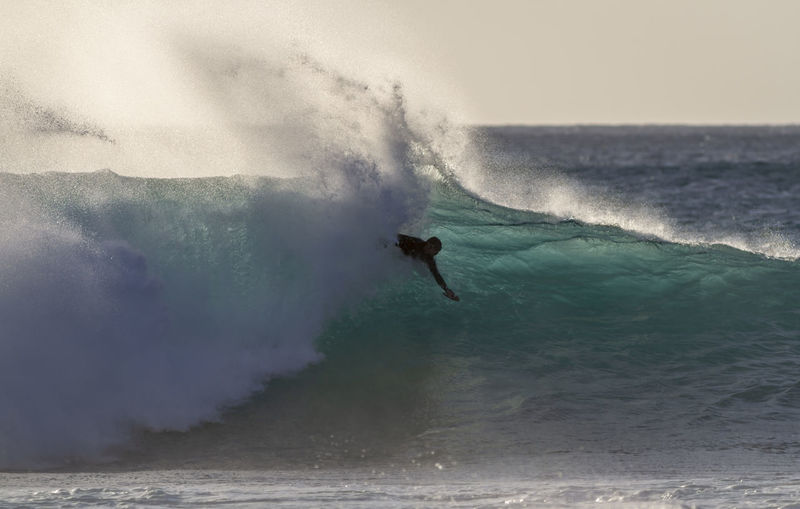 A body surfer riding a wave Hawaii Surf Adventure Aquatic Sport Beauty In Nature Day Leisure Activity Motion Nature North Shore One Person Outdoors Power Power In Nature Riding A Wave Sea Skill  Sky Sport Sunset Surfing Unrecognizable Person Waimea Bay Water Wave
