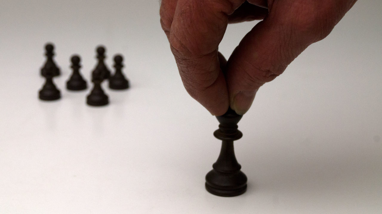 white background, human body part, human hand, studio shot, human leg, indoors, close-up, low section, men, competition, one person, chess piece, day, people