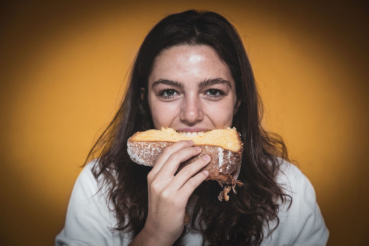 Portrait of young woman holding a slice of cake