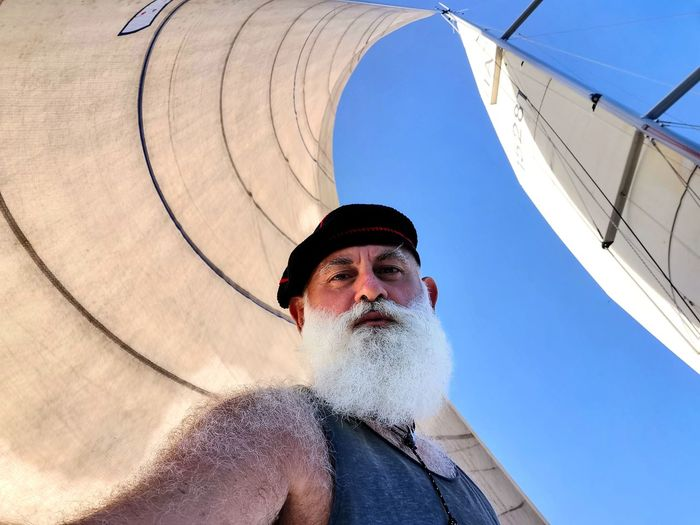 Low angle portrait of mature man standing on sailboat against sky