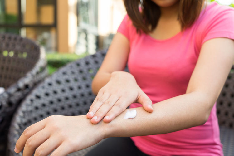 Close-up of woman applying cream on hand