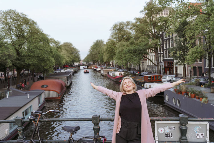 Woman standing on boats in canal along trees