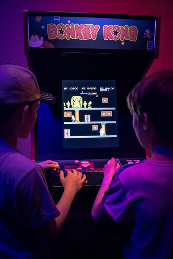 Gamers Arcade Games Arcade Old Fashioned Donkey Kong Nintendo Nintendolife Technology Indoors  Rear View Adult People Screen Occupation Two People Device Screen Communication Arts Culture And Entertainment Looking Headshot Motion Lifestyles Control Care Players Playing Videogames Video Games Gaming Gaming Time Screen