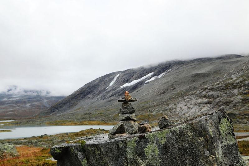 Rock stacking against sky