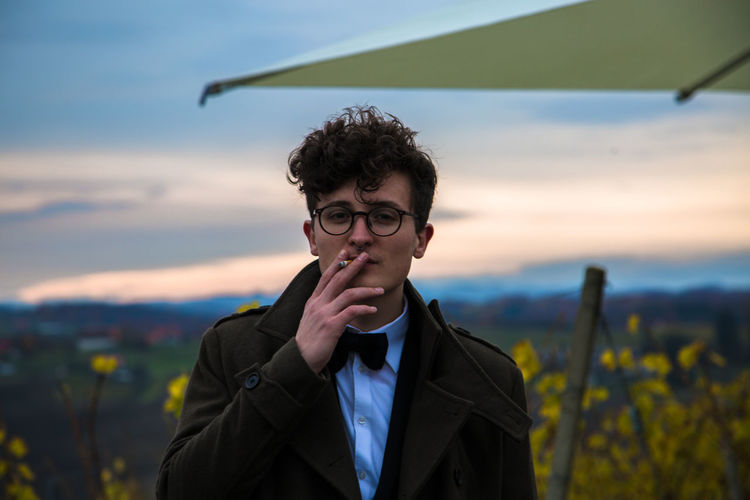 Smoking Suit Beauty In Nature Bowties Eyeglasses  Focus On Foreground Front View Hipster Lifestyles Nature One Person Outdoors Portrait Real People Sky Standing Young Adult Young Men