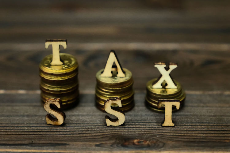 TAX CONCEPTUAL WITH STACKED COIN Accuracy Animal Representation Antique Art And Craft Close-up Creativity Figurine  Focus On Foreground Income Tax Return Indoors  Letter Metal No People Number Representation Selective Focus Still Life Table Text Toy Wood - Material