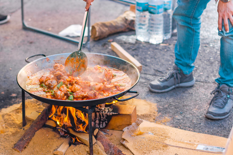 Paella preparation on the street during fallas festivity. Valencian chicken paella. Kitchen Utensil Food And Drink Food Preparation  Household Equipment Fire Burning Day Low Section Heat - Temperature Meat Fire - Natural Phenomenon Cooking Pan Human Leg Flame Outdoors Wood - Material Standing Preparing Food Camping Stove Paella Fallas València Hand Campfire