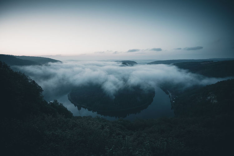 Bow if river Saar in Germany close to Orscholz before sunrise. Germany Saarschleife Scenics - Nature Beauty In Nature Sky Tranquil Scene Tranquility Mountain Cloud - Sky Nature No People Environment Non-urban Scene Tree Idyllic Landscape Day Outdoors Fog Moody Clouds Cloud And Sky This Week On Eyeem Morning Morning Light Morning Sky Landscape_Collection