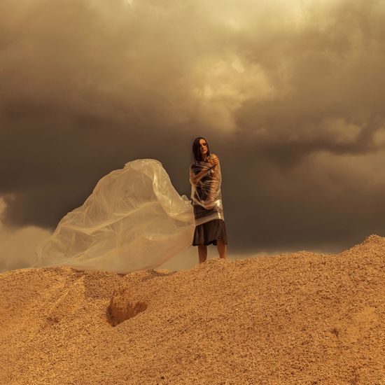 Low angle view of woman wrapped in plastic standing on sand dune against cloudy sky