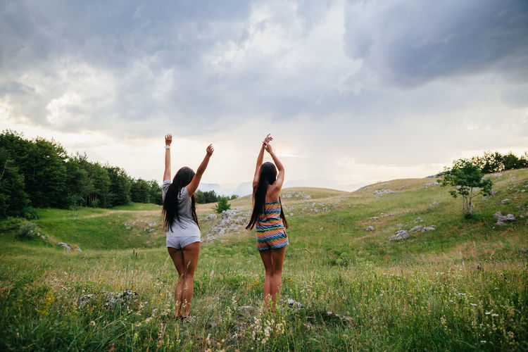 two girls happy jump in mountains with field view with rainy sky background. Two girls dancing happily Dance Dancing Happiness Happy Rainy Days Travel Adult Casual Clothing Cloud - Sky Countryside Field Friendship Grass Jumping Leisure Activity Outdoors Positive Emotion Sky Standing Togetherness Two People Village Life Women