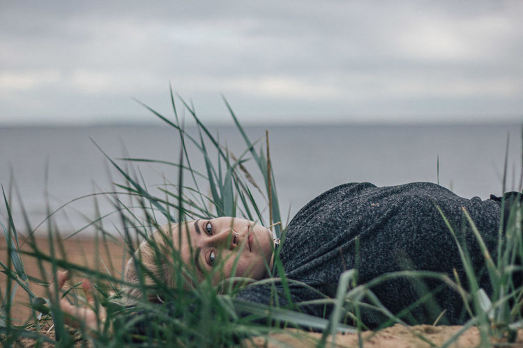 Portrait of young man lying on grass by sea against sky