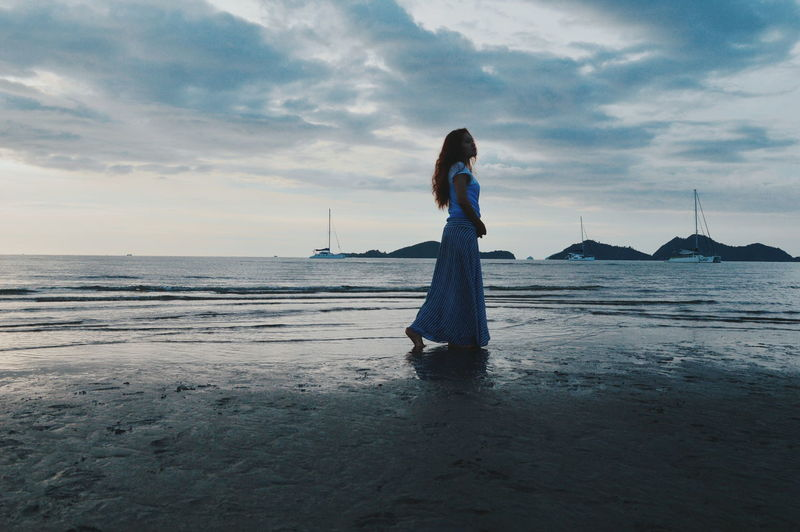 Woman Standing On Beach Against Sky
