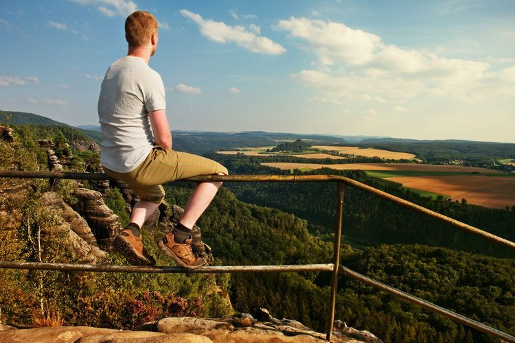 Short hair man sit on handrail at peak of rock and watch to land. hiker with grey shirt and pants