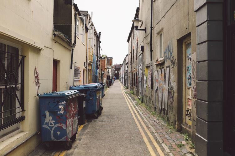 Garbage bins in alley amidst buildings at town