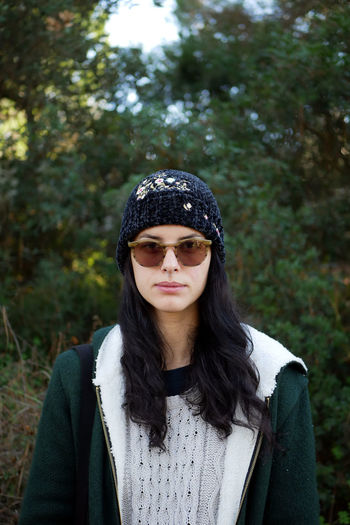 Portrait of beautiful young woman wearing sunglasses while standing against trees