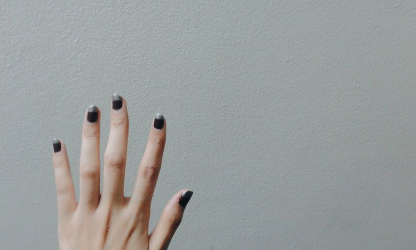 Close-Up Of Woman Hand With Nail Art Against Wall