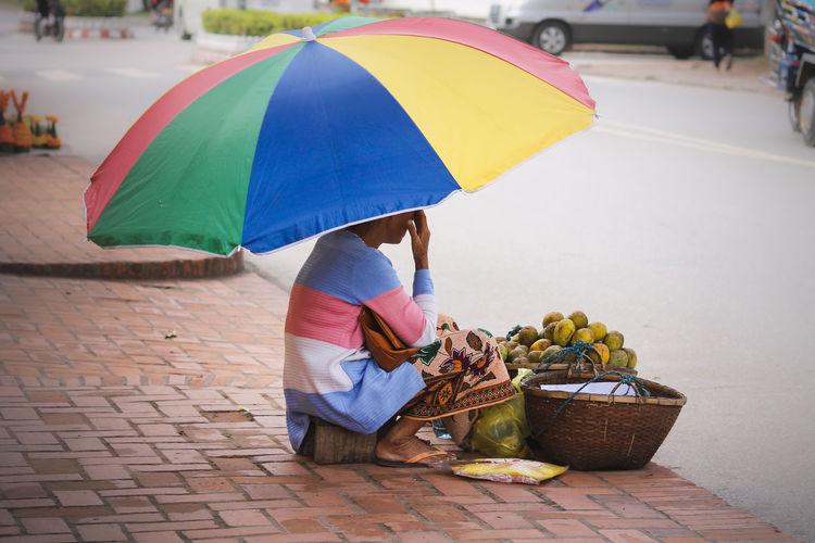 Woman selling mangoes on street