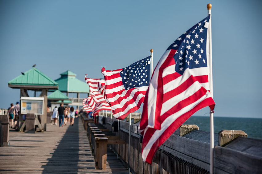 American flags lining a pier at a beach in Charleston, SC American Flag Americana Charleston SC Pier South Carolina Architecture Blue Clear Sky Day Flag Focus On Foreground Incidental People Independence Nature Ocean Outdoors Patriotism People Pride Shape Sky Striped Vacation Water Wind