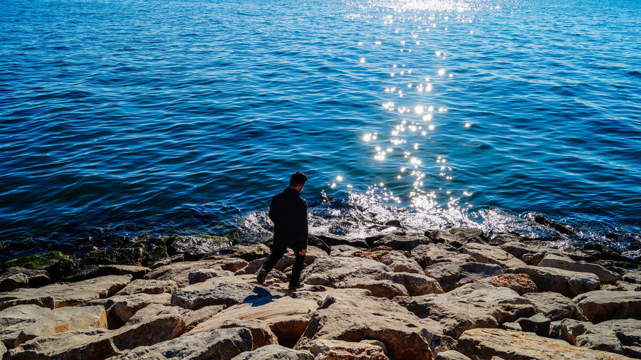 Rear View Of Man Standing On Rocks By Sea