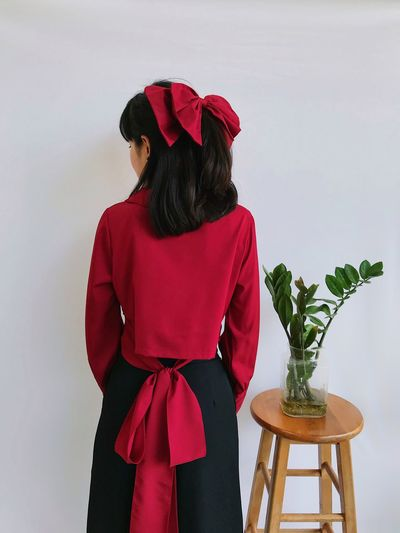 Rear view of woman with red umbrella standing against wall