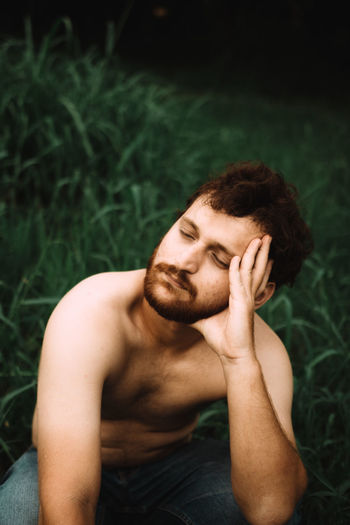 High angle view of shirtless young man crouching on grass