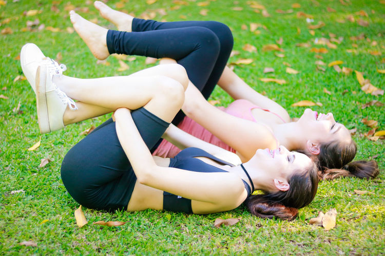 Side view of young female friends exercising on field