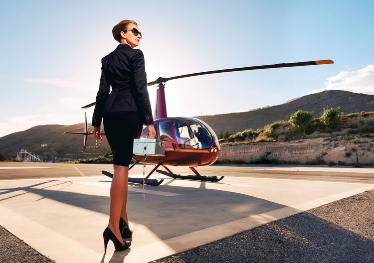 Low angle view of businesswoman holding box while standing by helicopter during sunny day