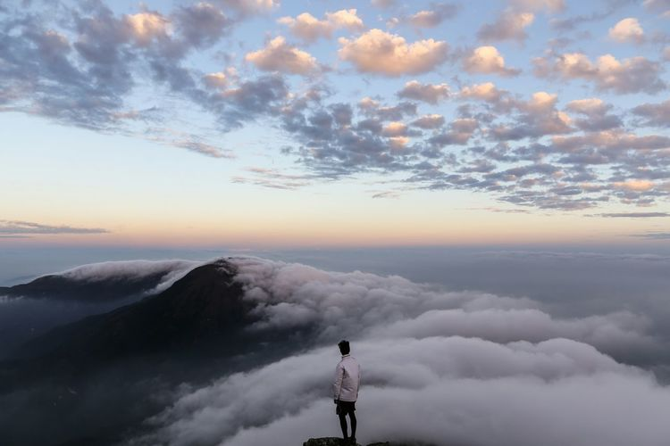 Man standing on cliff looking at cloudscape