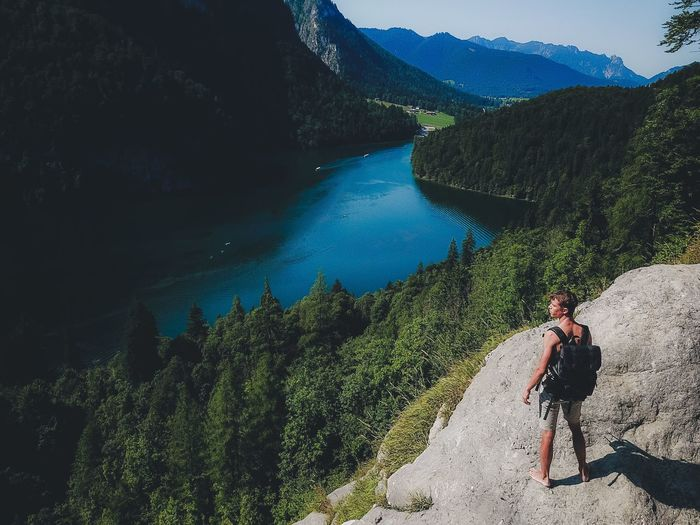 Man standing on cliff by lake against sky