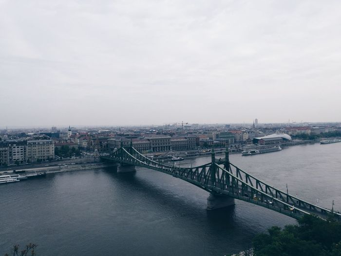 Bridge over river in city against cloudy sky