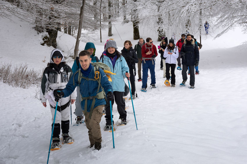 Subiaco, Italy - February 25, 2018: In the middle of winter, group of people take an excursion on the snow-covered mountain, wearing snowshoes on their feet to avoid sinking in the fresh snow, with the help of trekking poles. Adventure Cold Temperature Day Enjoyment Frozen Full Length Leisure Activity Lifestyles Looking At Camera Men Nature Outdoors Portrait Real People Ski Holiday Ski Pole Skiing Snow Standing Togetherness Vacations Warm Clothing Weather Winter Winter Sport