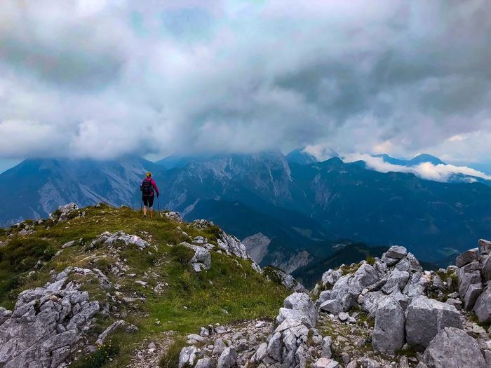 Rear view of backpacker looking at mountains against cloudy sky