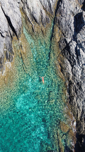 Aerial view of woman floating in sea by rocks