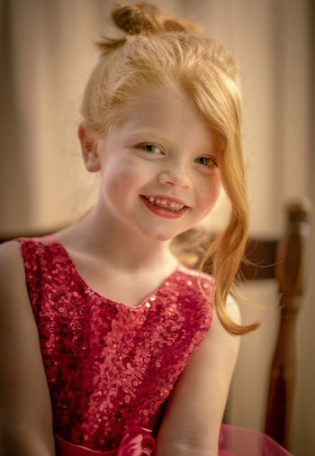 A five-year-old girl with red hair and blue eyes sits for a portrait with her hair up in a bun smiling at the camera. Childhood Child Happiness Smiling Portrait Hair Blond Hair Offspring Emotion Front View Looking At Camera One Person Girls Indoors  Cheerful Innocence Headshot Hairstyle Red Hair Blue Eyes Beauty Happiness Smile 85mm F1.4 Lens