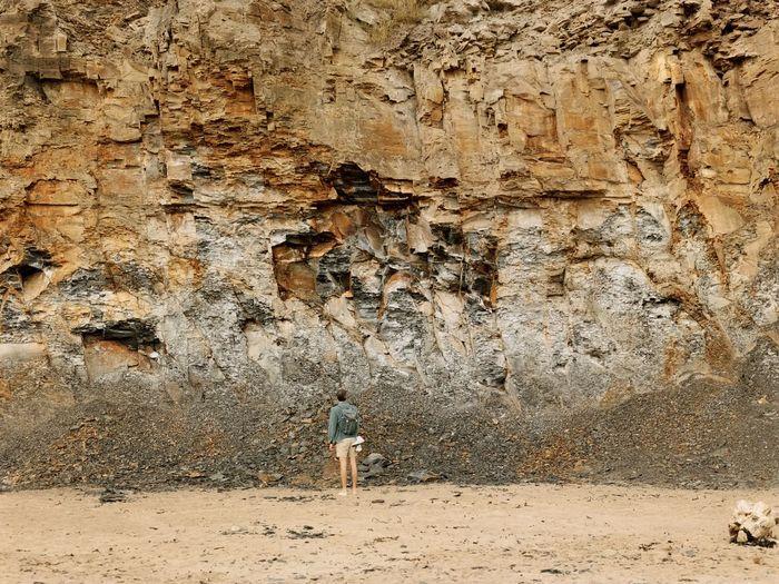 Rear view of a man walking on rock