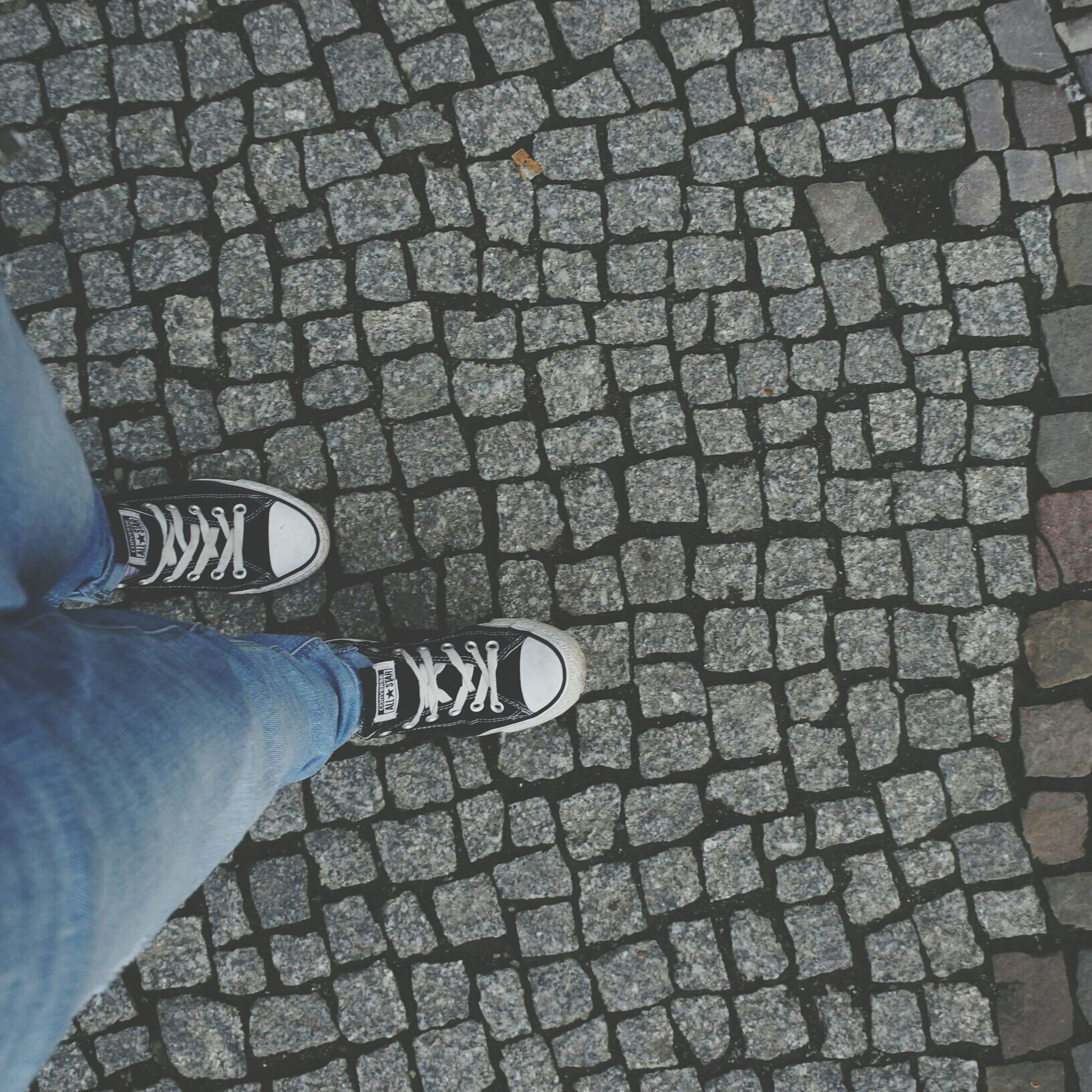 low section, high angle view, person, cobblestone, shoe, street, paving stone, standing, personal perspective, lifestyles, pattern, unrecognizable person, text, tiled floor, communication, footpath, sidewalk