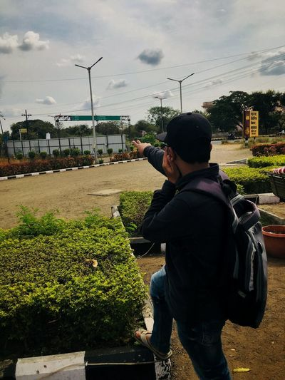 Rear view of boy against plants in city against sky