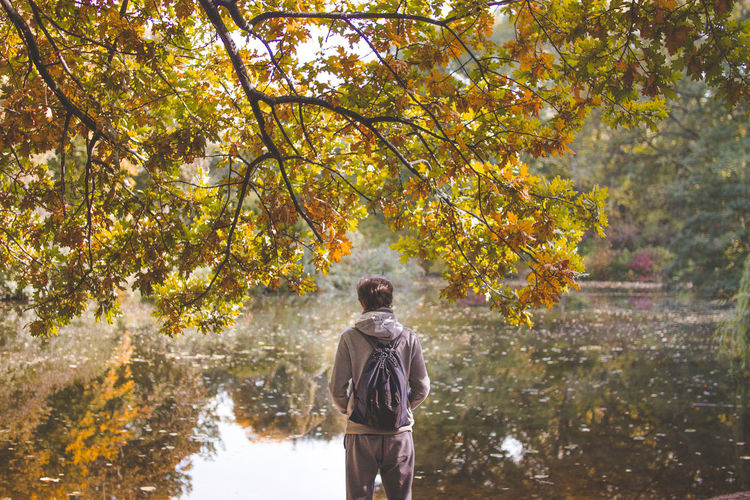 Rear View Of Male Hiker Standing At Lakeshore During Autumn