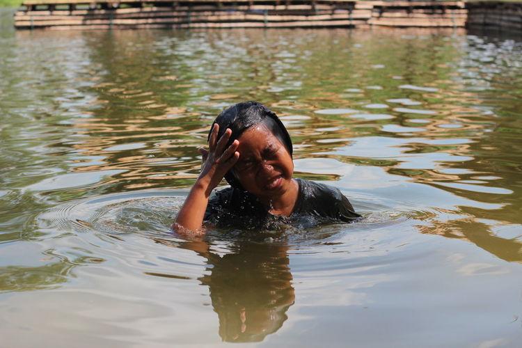 Portrait of shirtless man swimming in lake