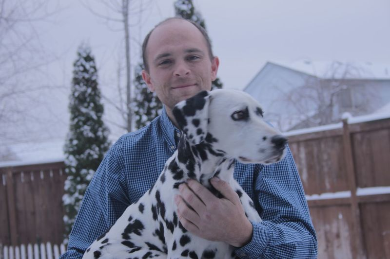Portrait of man holding dalmatian during winter