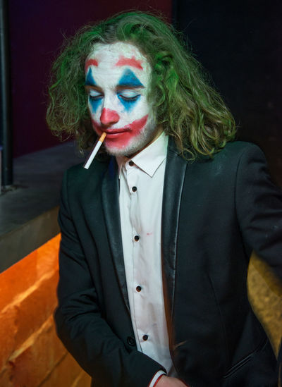 Man wearing clown make-up smoking cigarette while sitting indoors